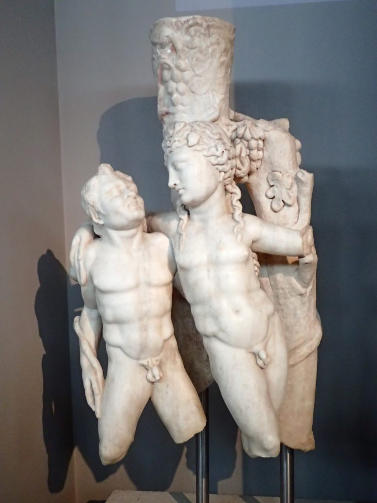 That's Dionysus embracing a satyr. What's that coming from the top of his head? This is a Trapezophoron- a table support. It dates from the time around the Pythian games.
