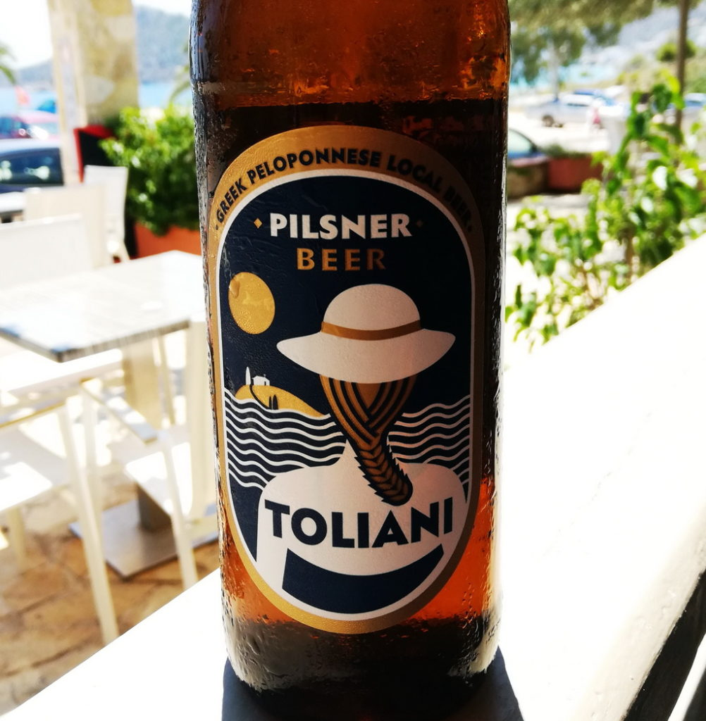 The Refreshing Ultra-local Pilsner - Toliani, has a sketch of a girl at the beach