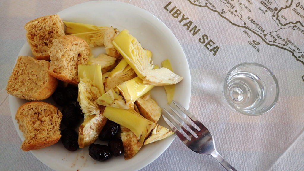 Great Greek drinks -a shot of tsicoudia with a plate of raw artichoke slices