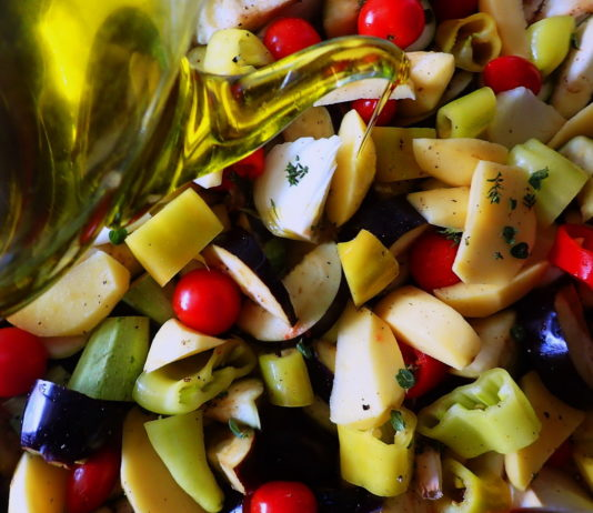Briam - tourlou, vegetables and fresh herbs, drizzled with olive oil and ready for the oven