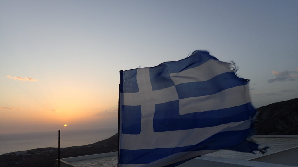 A Greek flag flying in the wind at sunset, high above the sea in Kasos