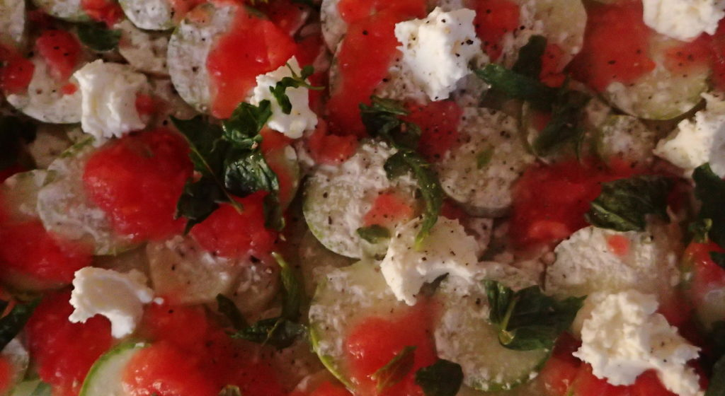 Layers of delicate slices of potato and zucchini are dotted with goat cheese and grated tomato, with fresh mint leaves