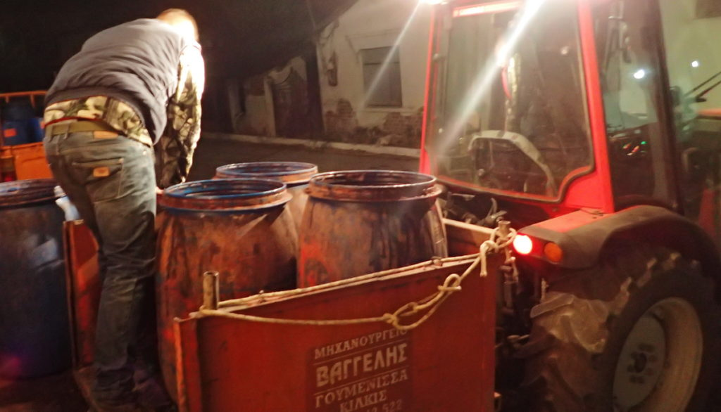 Vats of pomace for tsipouro arriving by tractor
