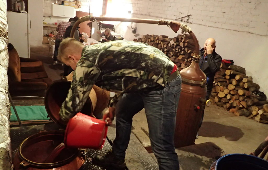 Filling the still with buckets of fermented grape mash