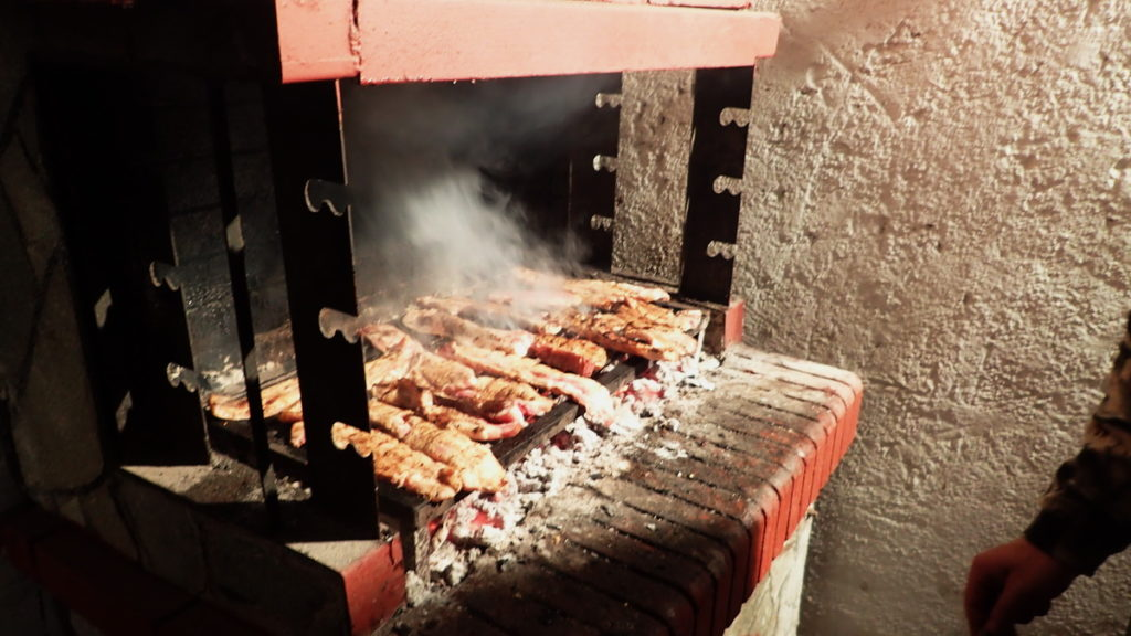 As the tsipouro distills, souvlakia char on the grill.