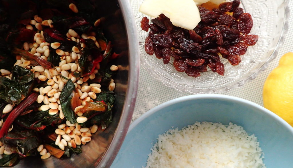 Filling ingredients for a Swiss chard tart - raisins, chard with pine nuts, and grated Parmesan cheese, in bowls