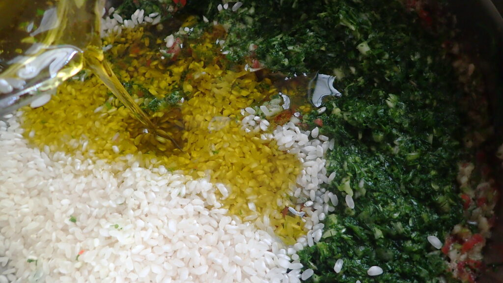 Pouring lots of extra virgin olive oil into the rice and herb mixture for stuffed grape leaves - dolmadakia gialantzi